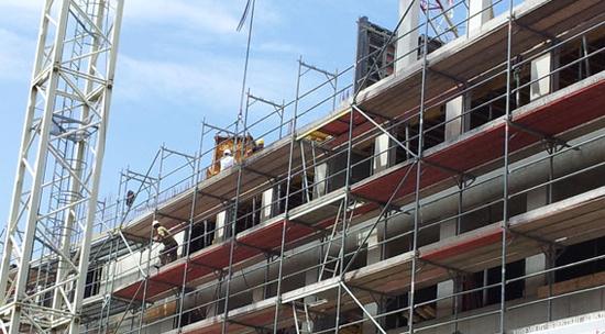 Beschäftigte auf sicherem Baugerüst